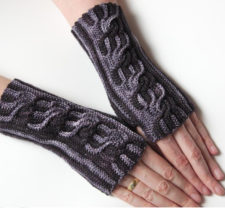 Twisting cabled fingerless mitts in two colors.