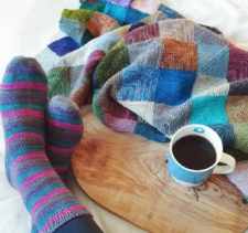 Mitered square blanket, and cup of coffee are on a table. Feet wearing knitted socks are resting on the table.