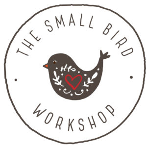 Hand-drawn circle with a Pennsylvania Dutch-style painted bird and the words The Small Bird Workshop