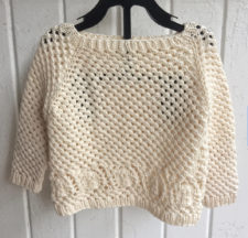 Baby sweater knitted with lots of openwork, and a shell border at the hem.