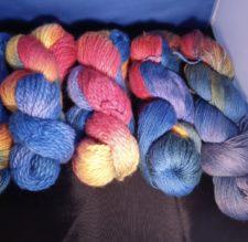 Various weights of yarn in rainbow variegated colorways.