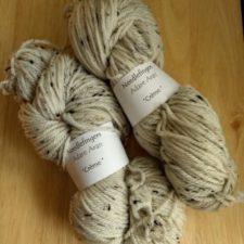 Two thick skeins of tweed yarn.