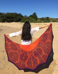 Woman on the beach holds large shawl with a sun design.