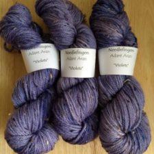 Three skeins of thick, tweed yarn in purple.
