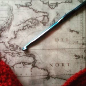 photo of an old map of the world, with a crochet hook on top of it