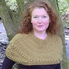 Designer Sally Pointer wears a beautiful bobbled shawl. In the background is a large tree.