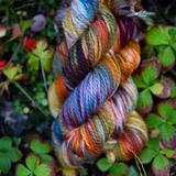 Bright, variegated yarn against leafy background