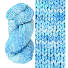 Blue sky color yarn with white variations like wispy clouds, skein and swatch