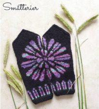 Dark mittens with flower design that extends across both mitten tops.