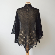 Large, triangular shawl in fine yarn, with wide lace panel on bottom two edges.