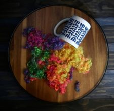 Rainbow hued locks spilling out of a coffee cup.
