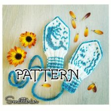 Baby mittens on a string, with colorwork mermaid on one and undersea plants on the other.