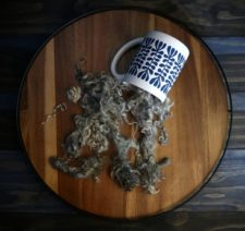 Natural locks spilling out of coffee cup.