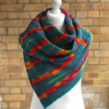 Small triangular shawl in stripies with yarnover openwork in some of the stripes.