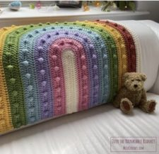 Baby blanket with curved rainbow that has same-color bobbles in each ring.