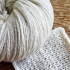 Swatch and ball of undyed yarn. Knits up a bit thick and thin.
