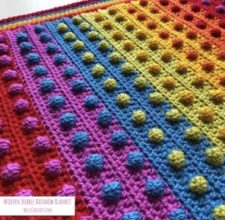 Rainbow striped baby blanket with contrasting bobbles every couple of inches.