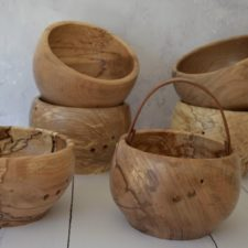 Wood yarn bowls with dramatic wood grain. Some have leather handles.