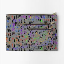 Light zippered pouch with print that has FBY and crescent moons and tiny Statues of Liberty, along with bright speckles.