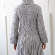 Long-sleeve thigh-length coat has several kinds of cables throughout.