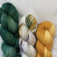 Three skeins, green leaves, gold flower and a variegated skein with both colors on a white base.