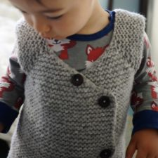 Baby or toddler vest buttons down left side.