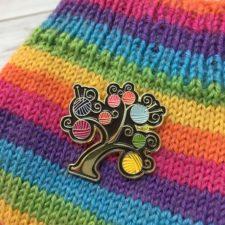 Enamel pin of balls of yarn as fruit on a tree.