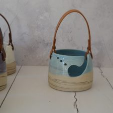Ceramic yarn bowl with large scoop opening and several small holes. Bowl has a leather strap handle.
