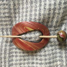 Red and gold modeling clay folded together to look like wood grain. Wooden stick pin has matching modeling clay ball.