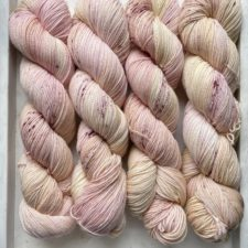 Four twisted skeins in creamy pastels like yogurt with fruit.