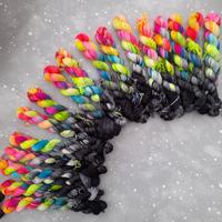 Array of skeins that are half tonal black and half neon rainbow.