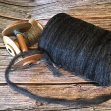 Black undyed roving and two wood spindles.