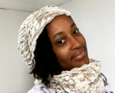 Tania looks over her shoulder smiling slightly, wearing a knitted hat and matching cowl.